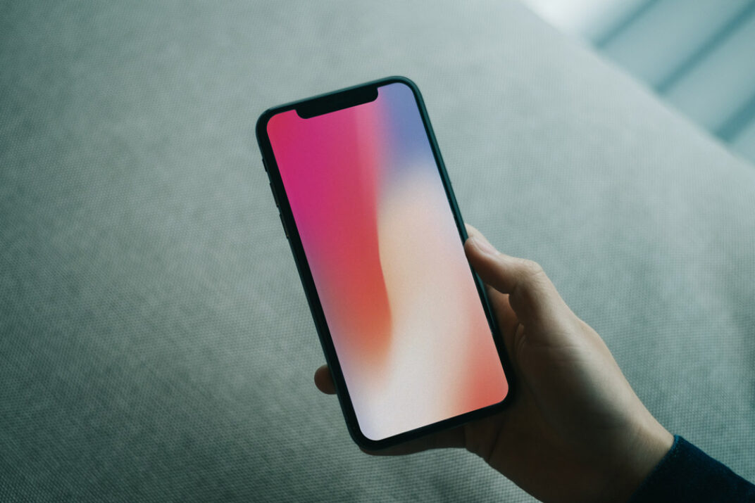 Hand holding iPhone X Mockup FREE download